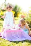 Två systrar som spelar tebjudningen utomhus Arkivfoton