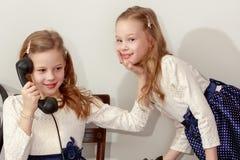 Två systrar som talar på den gamla telefonen Royaltyfri Foto