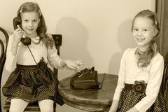 Två systrar som talar på den gamla telefonen Royaltyfri Fotografi