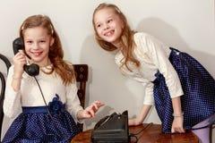 Två systrar som talar på den gamla telefonen Royaltyfri Bild