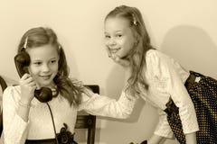 Två systrar som talar på den gamla telefonen Royaltyfria Foton