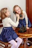 Två systrar som talar på den gamla telefonen Arkivbild