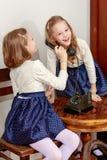 Två systrar som talar på den gamla telefonen Arkivbilder