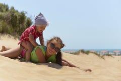 Två systrar spelar på en sandig strand royaltyfri bild