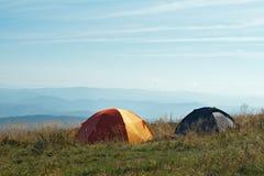 Två tält på höglands- alpint i dagsljus Arkivfoto