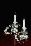 Två tända stearinljus i elegantnyhljusstakar Royaltyfri Fotografi