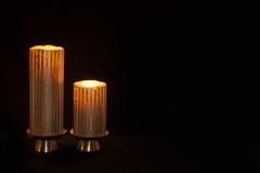 Två tända stearinljus mot en mörk beackground Arkivbilder