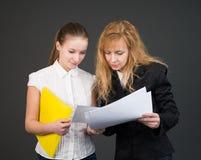 Två talande affärskvinnor med dokument. Arkivbilder