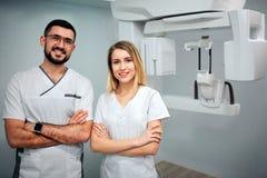 Två tandläkare står i röntgenstrålerum och poserar till kameran De ler och rymmer händer cossed Professionell på bild arkivfoton