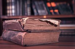 Två tappningböcker, gammal stil, med den suddiga bokhyllan på bakgrunden arkivfoto