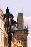 Två tappninggatalyktor med ett torn i bakgrunden Prague för republiktown för cesky tjeckisk krumlov medeltida gammal sikt Royaltyfri Foto