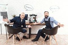 Två teknikerer arbetar i ett modernt laboratorium med en skrivare 3d De har pratsamma moln över deras huvud Royaltyfri Fotografi