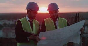 Två teknikerer har en diskussion om plan av konstruktion och att se till och med arket och minnestavlan, på slutinnehavet arkivfilmer