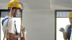 Två teknikerer i hardhats som har gyckel, medan arbeta på konstruktionsplatsen av byggnaden lager videofilmer
