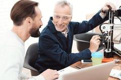 Två teknikerer skrivar ut detaljerna på skrivaren 3d En äldre man kontrollerar processen Royaltyfri Bild
