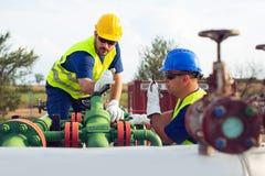Två teknikerer som arbetar inom fossila bränslenraffinaderi royaltyfri foto