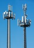 Två telekommunikationtorn med satelliter Arkivbilder