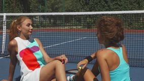 Två tennisflickor som talar, medan koppla av på domstolen stock video