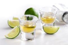 Två tequilaskott med limefruktskivan och saltar arkivbilder