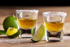 Två tequilaskott med limefruktskivan och saltar arkivfoto