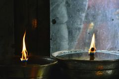 Två tibetana olje- lampor i den buddistiska bönen hyr rum nära fönstret, exponeringsglas som fördunklas och täckas med modeller Fotografering för Bildbyråer