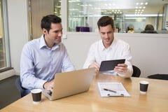 Två tillfälliga affärsmän som tillsammans arbetar i modernt kontor med la Royaltyfri Fotografi