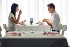 Två tillfälliga unga vuxna människor som har en konversation över ett mål Formellt förslag som talar i en restaurang Försökande m arkivfoto