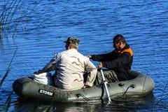 Två tjuvskyttar på ett lås för rubber fartyg fiskar i det netto Zhitomir Arkivbilder
