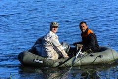 Två tjuvskyttar på ett lås för rubber fartyg fiskar i det netto Zhitomir Arkivfoton