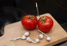 Två tomater och ung vitlök på träskärbräda Royaltyfri Foto