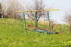 Två tomma barngungor och gungbräde på lekplatsaktiviteter offentligt parkerar/den naturliga miljön, gräs, fjädrar blommor Royaltyfri Fotografi