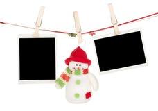 Två tomma foto och snögubbe som hänger på klädstrecket Arkivbilder