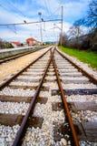 Två tomma järnväg linjer som sammanfogar i avståndet royaltyfria foton