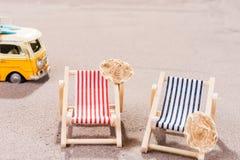 Två tomma strandstolar i sanden, med den gamla skåpbilen Royaltyfri Bild