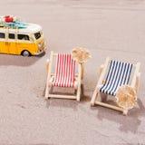 Två tomma strandstolar i sanden, med den gamla skåpbilen Fotografering för Bildbyråer