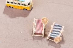 Två tomma strandstolar i sanden, med den gamla skåpbilen Arkivfoton