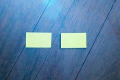 Två tomma vertikala affärskort för vit på ljust naturligt trä royaltyfri bild