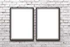 Två tomma vertikala målningar eller affischer i svart ram Arkivbild