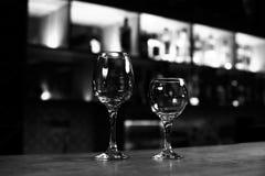 Två tomma vinexponeringsglas på stången kontrar det svartvita fotoet Royaltyfri Foto