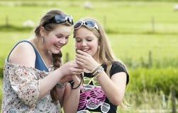 Två tonår som ser och skrattar royaltyfri fotografi