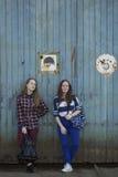 Två tonåriga flickor med ryggsäckar som står nära den gamla väggen Arkivbilder