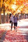 Två tonåriga flickor som tillsammans går under färgrikt höstlönnträd Arkivfoton