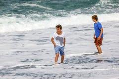 Två tonåriga pojkar har gyckel på stranden Fotografering för Bildbyråer