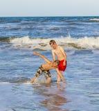 Två tonåriga pojkar slår ett roligt poserar i vågorna i det grova havet Royaltyfri Fotografi