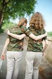 Två tonåriga vänner i skjortor för kamouflage t royaltyfri illustrationer