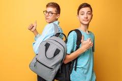 Två tonåringar, grabbar visar motsatta sinnesrörelser, vänner visar positiva och negativa gester, på en gul bakgrund arkivbild