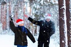Två tonåringar i julhattar Santa Claus som har gyckel i snen Fotografering för Bildbyråer