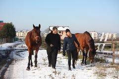 Två tonåringar och två hästar som går i snön Arkivbilder