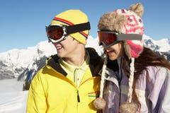 Två tonåringar skidar på ferie i berg Arkivfoton