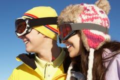 Två tonåringar skidar på ferie i berg Arkivbild